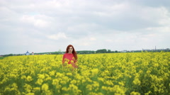 Pretty girl in the rape field walking and smiling to sky in 4k Stock Footage