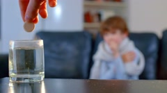 glass with effervescent tablet on the background of chilled, sick boy - stock footage
