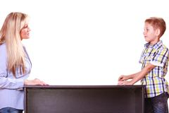 Mother and son talk and argue sit at table. Stock Photos