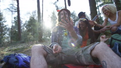 4K Happy hipster friends camping in the woods, playing guitar & singing Stock Footage