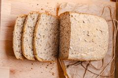 Sliced wholemeal bread on cutting board - stock photo
