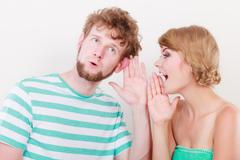 Woman telling an astonished man some secrets Stock Photos
