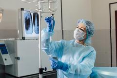Nurse connecting an intravenous drip in hospital room Stock Photos