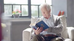 Elderly caucasian man reading a book and drinking a delicious tea in a modern Stock Footage