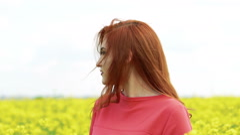 Happy woman smiling in the rape-field, horizon. Slow motion - stock footage