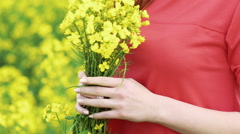 Close up girl smelling rape bouquet and smiling. Slow motion Stock Footage