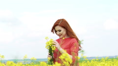 Woman with bouquet of rape blossom in the field, wind blowing. Slow motion Stock Footage