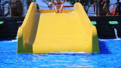 Happy child girls and boy sliding water park - stock footage