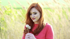 Pretty girl with golden hair blowing the dandelion on the background. Slowly Stock Footage