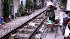 Saleswoman fruit in the Vietnamese hat with two baskets in the narrow streets Stock Footage
