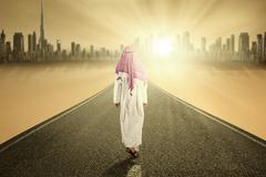 Arabic person walks on the road - stock photo