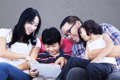 Family quality time on red sofa with touchpad - stock photo