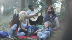 4K Happy hipsters camping in the woods, one man tells a story to his friends Stock Footage
