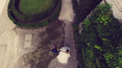 Drone, aerial. The camera shoots two newlyweds walking. Video vertically. N. Stock Footage