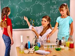 Children with teacher  in chemistry class. Stock Photos