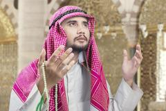 Muslim man praying with chaplet in mosque Stock Photos