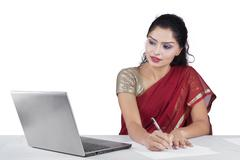 Woman with sari clothes working on desk Stock Photos
