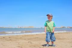 Cute small boy standing on the beach Stock Photos