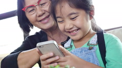 Little Asian girl using smart phone with her grandmother, Tilt up shot Stock Footage