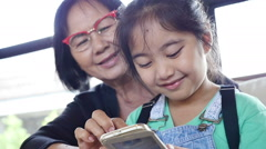 Little Asian girl using smart phone with her grandmother, Pan shot Stock Footage