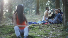 4K Happy hipster friends camping in the woods, girl turns to smile at camera Stock Footage