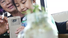 Little Asian girl using smart phone with her grandmother, Slow motion shot Stock Footage