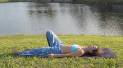 Girl practicing setu bhanda sarvangasana outdoors on the grass near lake Stock Footage