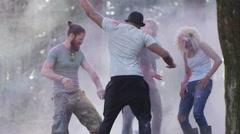 4K Happy hipster friends at music festival, dancing & throwing coloured powder.  - stock footage
