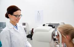Optician with tonometer and patient at eye clinic Stock Photos