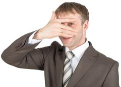 Surprised young man hiding eyes behind his hand - stock photo