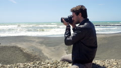 Handome man taking pictures with professional camera in front of the ocean Stock Footage