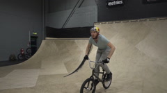 BMX'er Riding Indoor Skatepark - 3 axis gimbal tracking shot - Shot 3 of 3 - stock footage