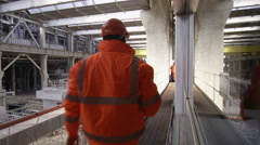 4K Interior view of industrial power plant & engineers walking through building Stock Footage