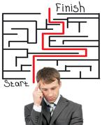 Thinking businessman in front of labyrinth - stock photo