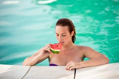 Portrait of sexy woman with piece of watermelon on pool - stock photo