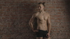Athletic shirtless man near brick wall. Lights of and on - stock footage
