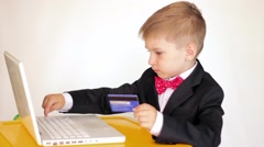 Cute little business kid boy use laptop and credit card Stock Footage