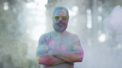 4K Portrait of serious hipster guy being covered in coloured powder at festival Stock Footage