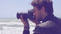 Handome man taking pictures with professional camera in front of the ocean cl Stock Footage