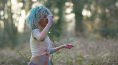4K Portrait of happy high energy girl throwing coloured powder at festival Stock Footage