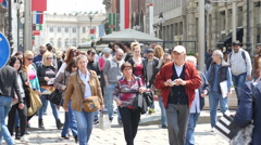 Crowd people tourists walking on pedestrian shopping street in Milan Italy Stock Footage