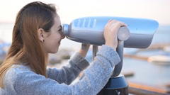 Young woman looking through stationary binoculars. Stock Footage