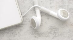 Headphones and cell phone in close up on stone table with slow sliding motion Stock Footage