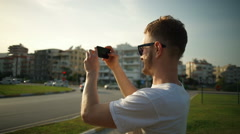 handsome man wearing sunglasses taking picture by smartphone slow motion - stock footage