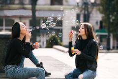 Two young adult girls on a city street - stock photo