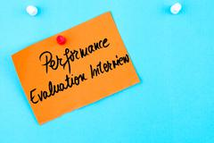 Performance Evaluation Interview written on orange paper note - stock photo