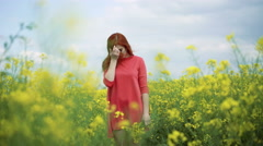 Girl with bouquet of rape blossom in the field, wind blowing, cloudy sky 4k Stock Footage