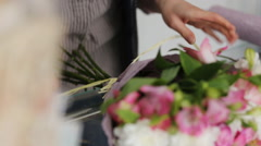 Close-up of bouquet making process in a flower store - stock footage