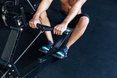 Muscular fitness man using rowing machine in the gym Stock Photos