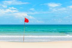 Red flag on tropical beach Stock Photos